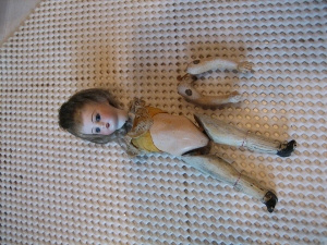 Bisque doll with detached arms.